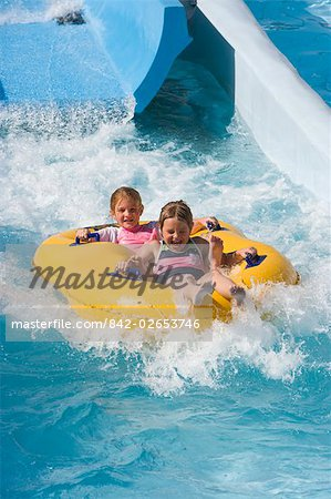 Sisters sliding down water slide on innertube in water park Stock Photo - Rights-Managed, Image code: 842-02653746