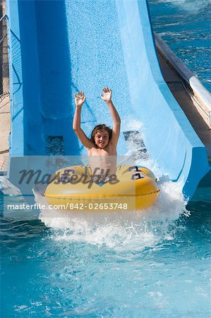 Boy sliding down water slide on innertube in water park Stock Photo - Rights-Managed, Image code: 842-02653748