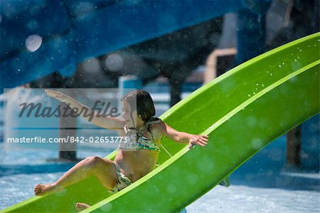Girl sliding down waterslide at water park Stock Photo - Rights-Managed, Image code: 842-02653773