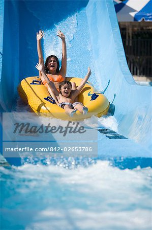 Portrait of mother and son sliding down water slide together on innertube in water park Stock Photo - Rights-Managed, Image code: 842-02653786