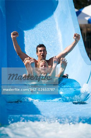 Portrait of father and daughter sliding down water slide together on innertube in water park Stock Photo - Rights-Managed, Image code: 842-02653787