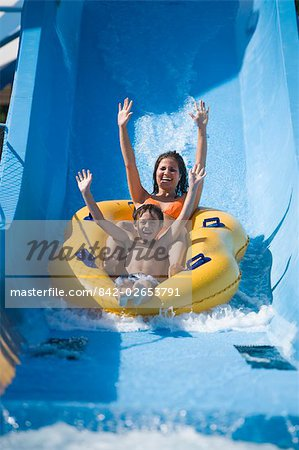 Mother and son sliding down water slide together on innertube in water park Stock Photo - Rights-Managed, Image code: 842-02653791