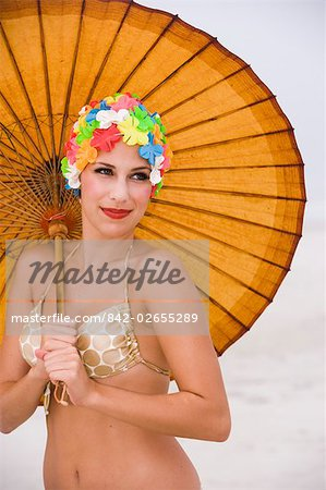 Young woman in retro swim cap holding umbrella on beach Stock Photo - Rights-Managed, Image code: 842-02655289