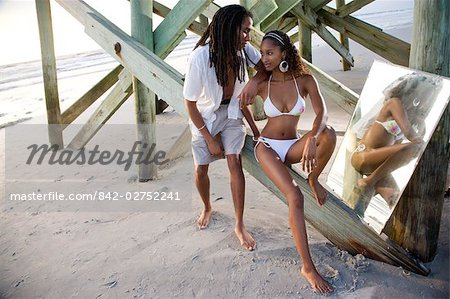 Portrait of young Jamaican couple sitting on beach pier with mirror Stock Photo - Rights-Managed, Image code: 842-02752241
