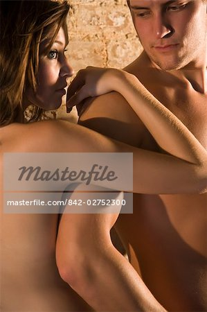 Portrait of young nude couple leaning against wall, looking at each other Stock Photo - Rights-Managed, Image code: 842-02752300