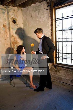 Portrait of young man in tuxedo handing nude woman in chair a flower Stock Photo - Rights-Managed, Image code: 842-02752330