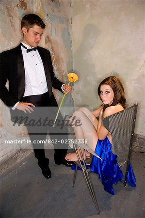Portrait of young man in tuxedo handing nude woman in chair a flower Stock Photo - Rights-Managed, Image code: 842-02752338