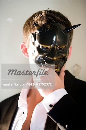 Portrait of young man in tuxedo holding masquerade mask Stock Photo - Rights-Managed, Image code: 842-02752372