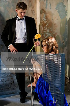 Portrait of young man in tuxedo holding a flower and nude woman in chair Stock Photo - Rights-Managed, Image code: 842-02752378