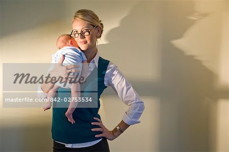 Portrait of young businesswoman holding baby standing against wall Stock Photo - Rights-Managed, Image code: 842-02753534