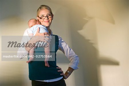 Portrait of young businesswoman holding baby Stock Photo - Rights-Managed, Image code: 842-02753564
