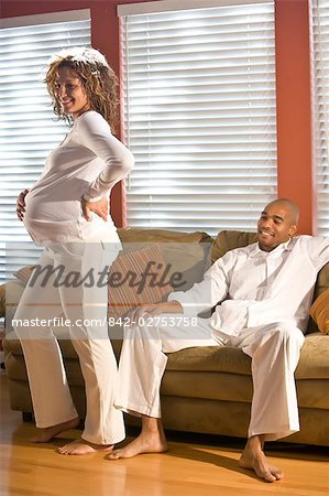 Portrait of pregnant African American woman standing in living room, man sitting on sofa Stock Photo - Rights-Managed, Image code: 842-02753758