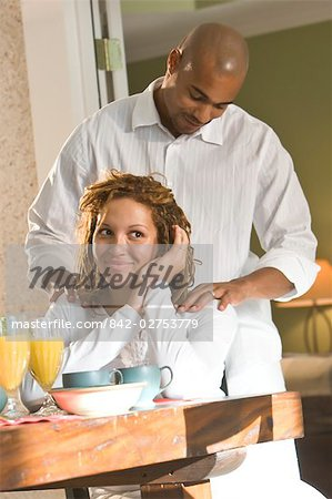 Portrait of African American woman sitting at table, man massaging shoulders Stock Photo - Rights-Managed, Image code: 842-02753779