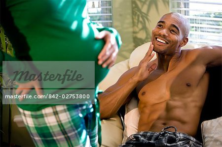 Pregnant woman posing for grinning African American man sitting on couch Stock Photo - Rights-Managed, Image code: 842-02753800