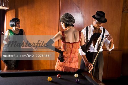 Portrait of African American man playing billiards as woman in flapper dress touches him Stock Photo - Rights-Managed, Image code: 842-02754564