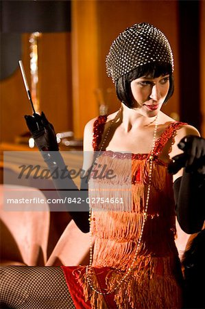 Portrait of woman in flapper dress sitting at bar with cigarette in the 1920s Stock Photo - Rights-Managed, Image code: 842-02754661