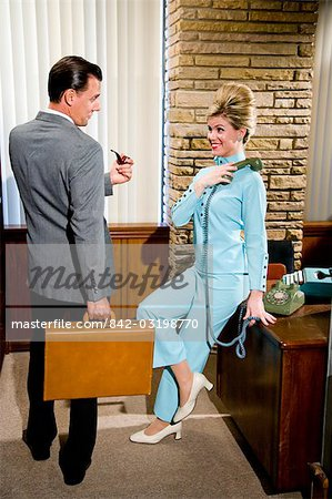 Vintage portrait of young secretary with phone and businessman holding briefcase Stock Photo - Rights-Managed, Image code: 842-03198770