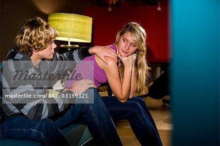 Thoughtful young teenage couple sitting on sofa indoors Stock Photo - Rights-Managed, Image code: 842-03199321