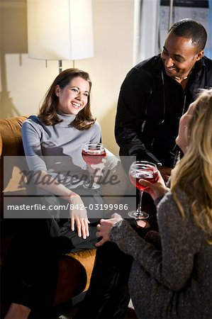 Multi-ethnic group of friends having a drink together in living room Stock Photo - Rights-Managed, Image code: 842-03199986