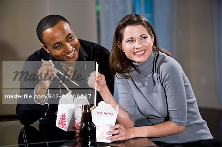 Multi-ethnic couple eating Chinese take-out in modern loft Stock Photo - Rights-Managed, Image code: 842-03200007