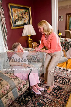 Adult daughter helping senior mother with cane in living room Stock Photo - Rights-Managed, Image code: 842-03200032