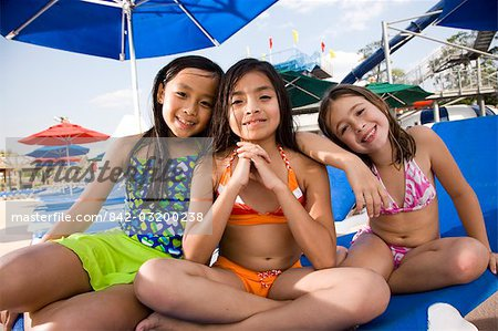 Multi-ethnic girls in swimsuits sitting on lounge chair in water park Stock Photo - Rights-Managed, Image code: 842-03200238