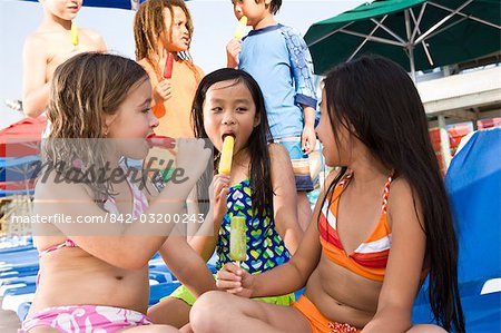 Multi-ethnic children wearing swimsuits eating popsicles Stock Photo - Rights-Managed, Image code: 842-03200243