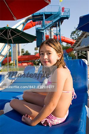 Young girl in swimsuit sitting on deck chair at water park Stock Photo - Rights-Managed, Image code: 842-03200277