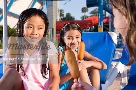 Three young girls at water park eating corn dogs stock photo premium