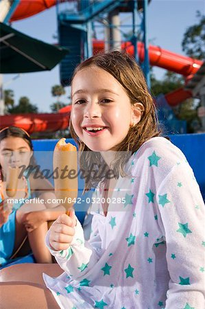 Young girl eating corn dog at water park in summer Stock Photo - Rights-Managed, Image code: 842-03200285