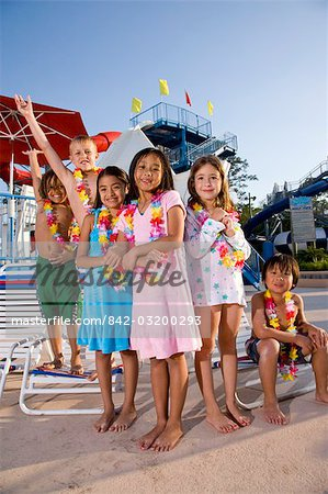 Multi ethnic children at water park in summer wearing flower leis
