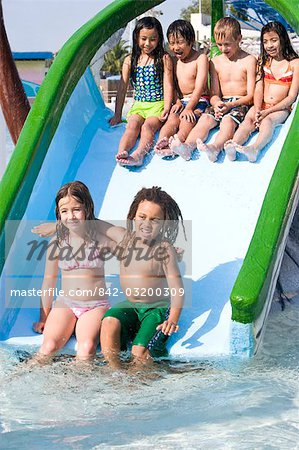 Multi-ethnic children on slide at water park in summer Stock Photo - Rights-Managed, Image code: 842-03200309