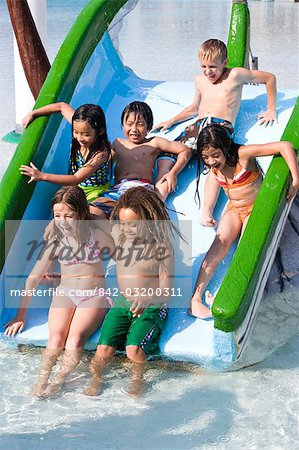 Group of children sliding down waterslide together Stock Photo - Rights-Managed, Image code: 842-03200311