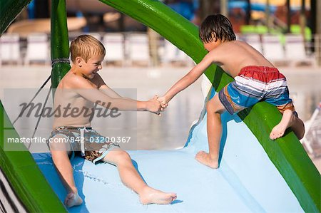 Two boys at water park in summer playing on slide near pool Stock Photo - Rights-Managed, Image code: 842-03200367
