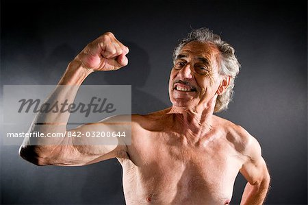 Senior man flexing muscles against gray background Stock Photo - Rights-Managed, Image code: 842-03200644