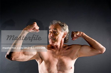 Senior man flexing muscles against gray background Stock Photo - Rights-Managed, Image code: 842-03200645