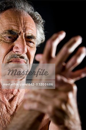 Close-up of senior man rubbing his sore hand Stock Photo - Rights-Managed, Image code: 842-03200686