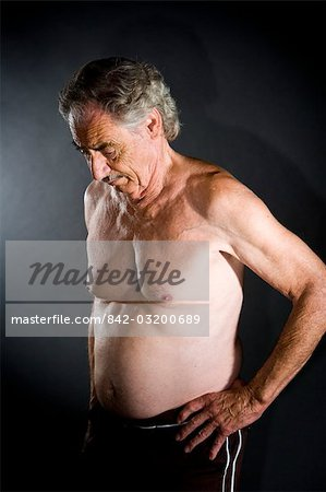 Depressed bare-chested senior man in short looking down, studio shot Stock Photo - Rights-Managed, Image code: 842-03200689