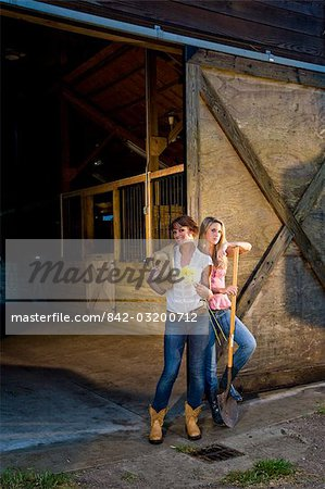 Mother and teenage daughter with flowers standing in front of stable Stock Photo - Rights-Managed, Image code: 842-03200712