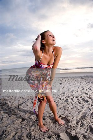 Happy young woman in colorful sundress standing on beach laughing Stock Photo - Rights-Managed, Image code: 842-03200998