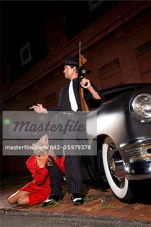 Gangster with Tommy gun, girlfriend clinging to leg Stock Photo - Rights-Managed, Image code: 842-05979378