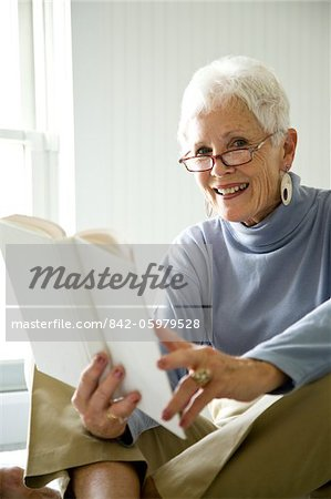 Portrait of senior woman sitting on bed with book smiling Stock Photo - Rights-Managed, Image code: 842-05979528