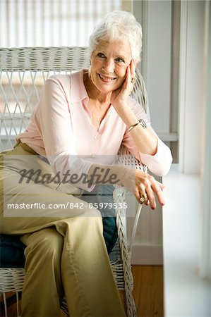 Portrait of senior woman sitting near window leaning on sill Stock Photo - Rights-Managed, Image code: 842-05979535