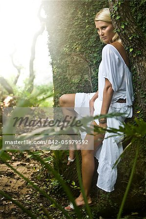 Sexy young blonde woman in white sitting on tree trunk Stock Photo - Rights-Managed, Image code: 842-05979592