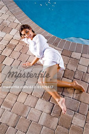 Portrait of mid-adult woman lying down next to swimming pool Stock Photo - Rights-Managed, Image code: 842-05979617