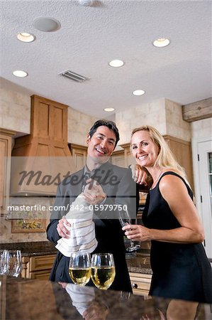 Mid-adult interracial couple opening bottle of champagne in kitchen of home Stock Photo - Rights-Managed, Image code: 842-05979750