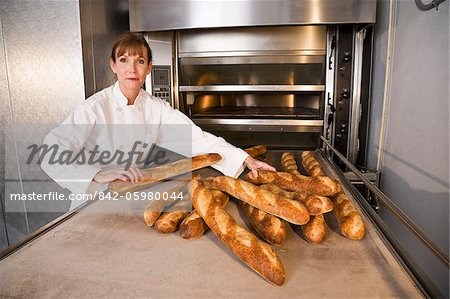 Mature woman taking baked loaves of bread out of commercial baker oven Stock Photo - Rights-Managed, Image code: 842-05980044