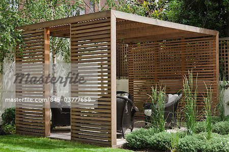 Slatted cedar pavilion on the right side of the lawn on the upper level of the garden. Silver birches along the boundary wall. Hebe and grasses on the right. Architects: Modular Stock Photo - Rights-Managed, Image code: 845-03777659