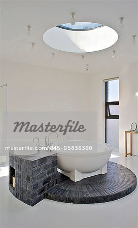 Bathroom, with a circular skylight that allows light to flood down onto the circular bath and its brick plinth. House of an art collector on the northern outskirts of Beijing. Designed by neighbouring artist Shao Fan, who also designed the furniture, this is part of a compound of several friends. Stock Photo - Rights-Managed, Image code: 845-05838380