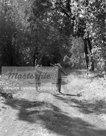 1940s 1950s TWO BOYS IN DUNGAREES PLAID SHIRTS STRAW HATS WALKING DOWN DIRT ROAD CARRYING FISHING POLES & CAN OF BAIT